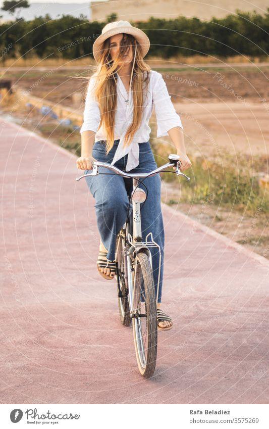 Junges Mädchen fährt mit dem Fahrrad durch die Natur Lifestyle jung Mitfahrgelegenheit wild altehrwürdig blond Frau