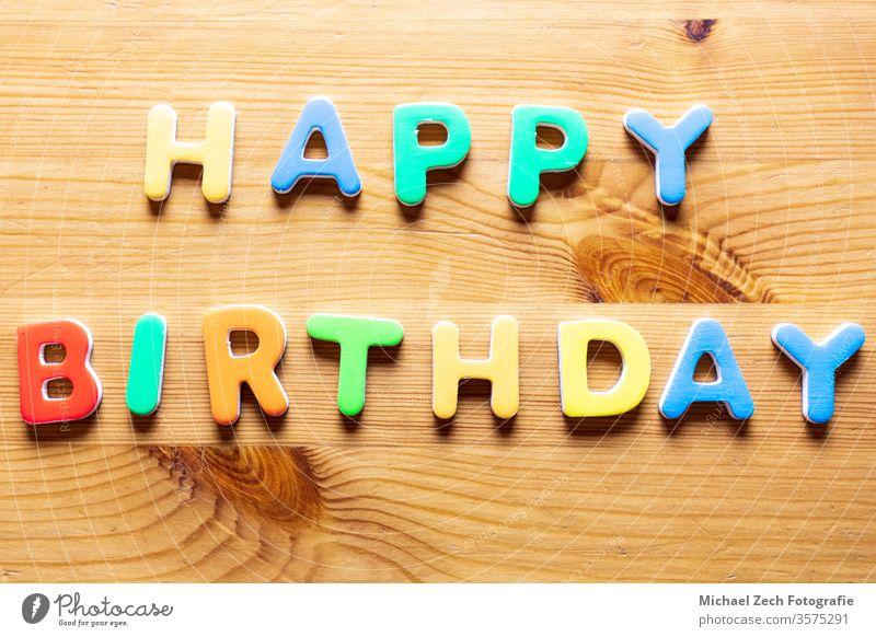 Mit bunten Buchstaben geschriebene Happy Birthday-Worte auf Holzuntergrund Brief Feiertag Geburtstagsfeier horizontal Spaß Postkarte heiter Bändchen Glückwunsch