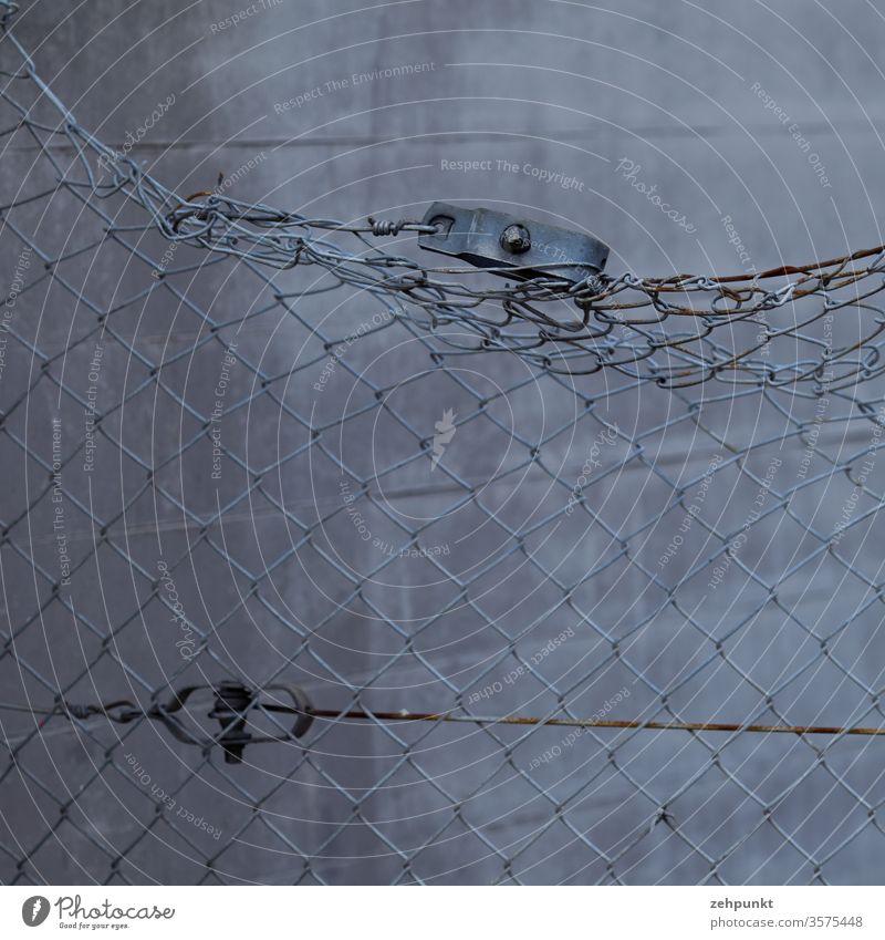 Ein verbogener Maschendrahtzaun vor einer grauen Betonwand Zaun Rost Oberkante Raster