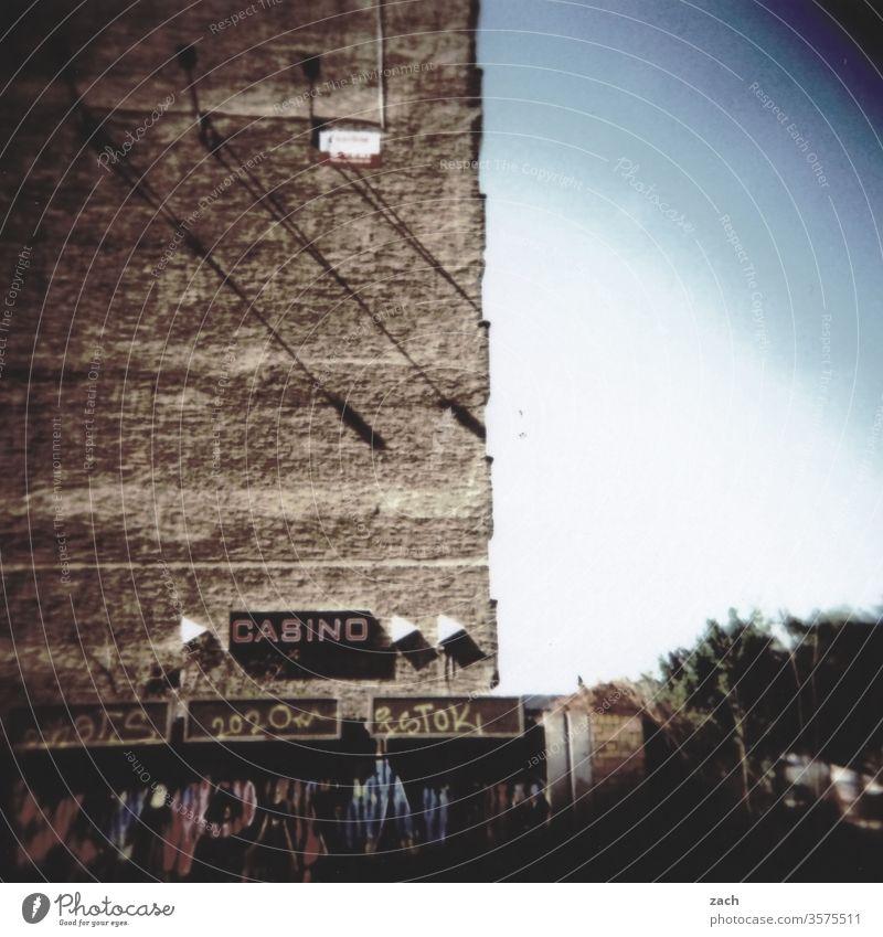 analoge Darstellung einer alten Hauswand mit der Aufschrift Casino Dia Stadt Himmel düster cross Cross Processing Experiment Holga Lomografie Scan Buchstaben