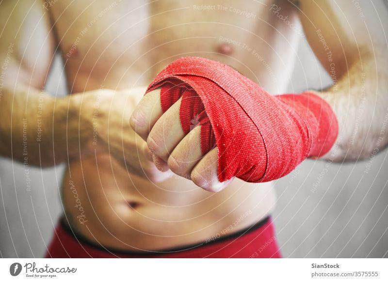 Der Mann umhüllt seine Hände mit roten Boxentüchern. Boxer Hand Wraps umhüllen Boxsport kämpfen Arme Hintergrund Handgelenk Athlet Kämpfer Fitness stark