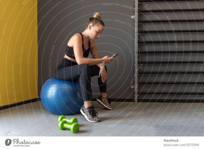 Sportlerin, die nach dem Training oder der Übung im Fitnessstudio sitzt, sich ausruht und ihr Handy beobachtet. App Mobile Telefon sportlich schlank Pause