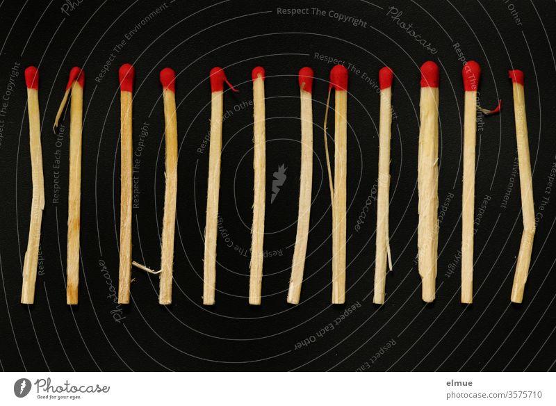 """Photochallenge I 12 """"anormale"""" Streichhölzer nebeneinander auf schwarzem Grund Streichholz Streichholzkopf Abweichung anders sein zwölf Dutzend brennen heiß"""