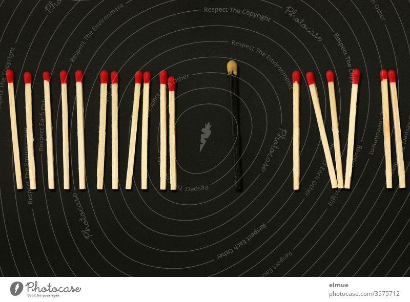Photochallenge I eine Reihe Streichhölzer mit roten Köpfen sowie ein schwarzes Streichholz mit gelbem Kopf auf schwarzem Grund Streichholzkopf sortiert