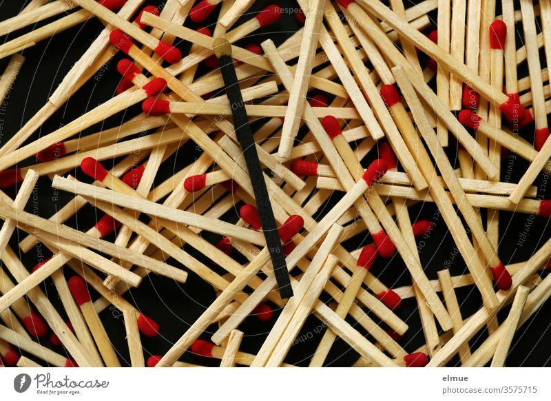 Photochallenge I viele Streichhölzer mit roten Köpfen sowie ein schwarzes Streichholz mit gelbem Kopf auf schwarzem Grund Streichholzkopf Individualist