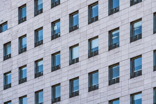 Fensterreihen eines Geschäftsgebäudes aus römischem Travertinmarmor Gebäude Fassade Murmel Architektur architektonisch urban Farbe Struktur abstrakt im Freien