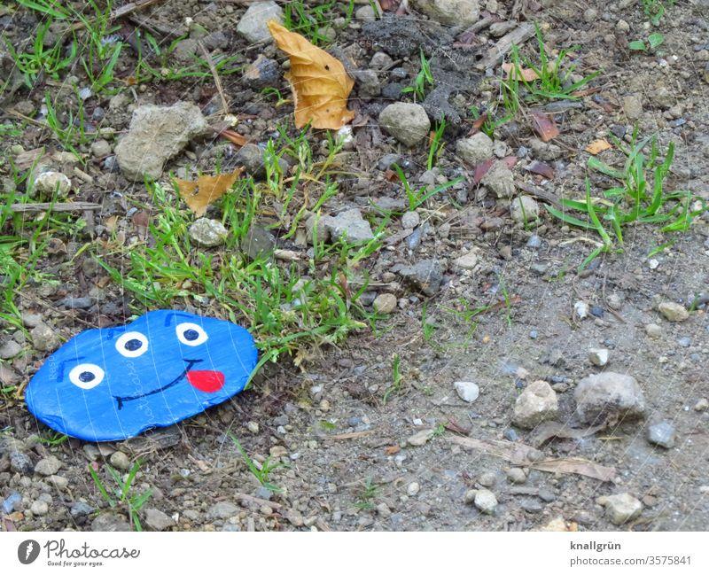 Ein blauer Glücksstein mit einem lustigen Monstergesicht mit drei Augen und herausgestreckter Zunge am Wegesrand Glückssteine Freude Wunschstein bemalt