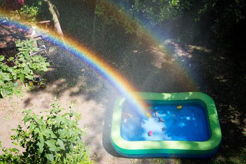 Regenbogen über einem Kinderplanschbecken in einem Garten Planschbecken Wasser Spielzeug Wassertropfen sprühnebel Sonnenlicht Kindheit draußen Schönes Wetter
