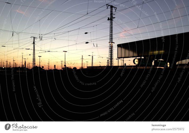 Dortmunder Bahnhof in der Dämmerung Gleise Dunkelheit Abend Nacht Bahnsteig Uhr Strommast Glas schwarz Außenaufnahme Eisenbahn Verkehr Bahnfahren Menschenleer