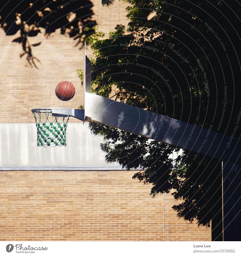 Basketball, roter Ball im Flug auf den Korb Basketballkorb Wand Netz Fassade Farbe Backstein Backsteinwand Backsteinfassade menschenleer Mauer Außenaufnahme
