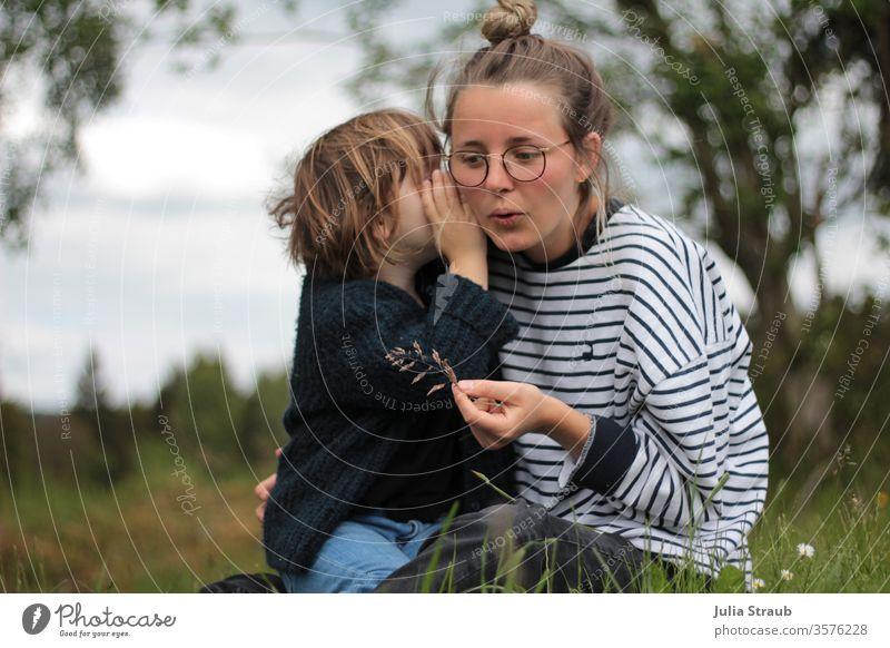 Mädchen flüstert Frau mit Brille etwas ins Ohr hören zuhören Flüstern Wiese Blume Wald gestreift gestrickt blau weiß grün Brillenträger Hipster Dutt Kind