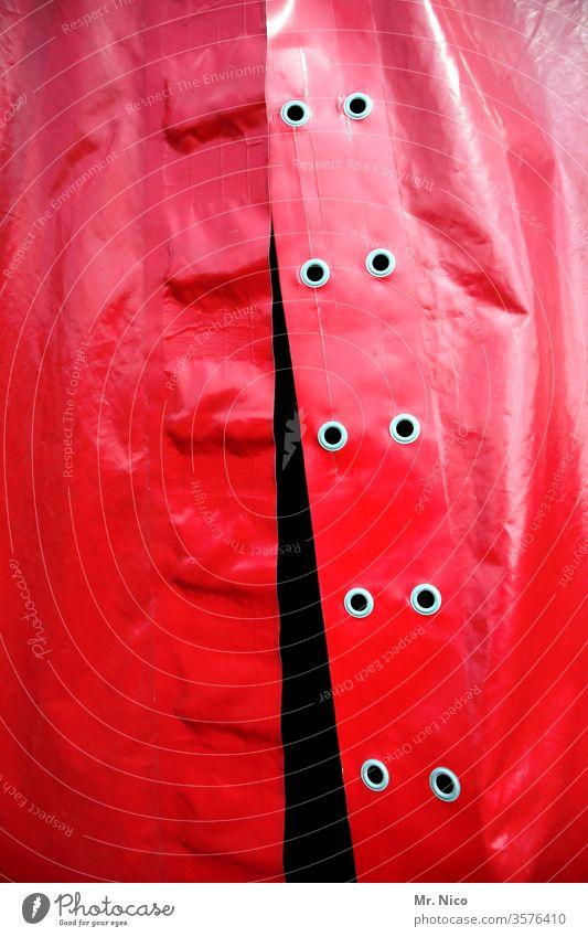 Plane eines Zirkuszelt rot Schutz abdeckung offen Eingang Nieten Detailaufnahme Abdeckung Strukturen & Formen Kunststoff geheimnisvoll Bühne Veranstaltung