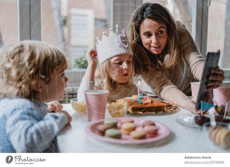 Fröhliches kleines Mädchen macht während der Geburtstagsfeier einen Videoanruf auf Tablet Mutter Tochter feiern Spaß Glück abgelegen heimwärts Entfernung