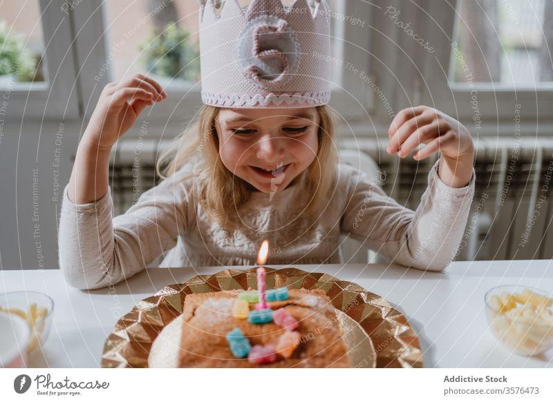 Kleines Mädchen bläst Kerze auf Geburtstagskuchen während einer Party zu Hause Kuchen Wunsch Schlag Glück feiern heimwärts Freude charmant Krone Filz dekorativ