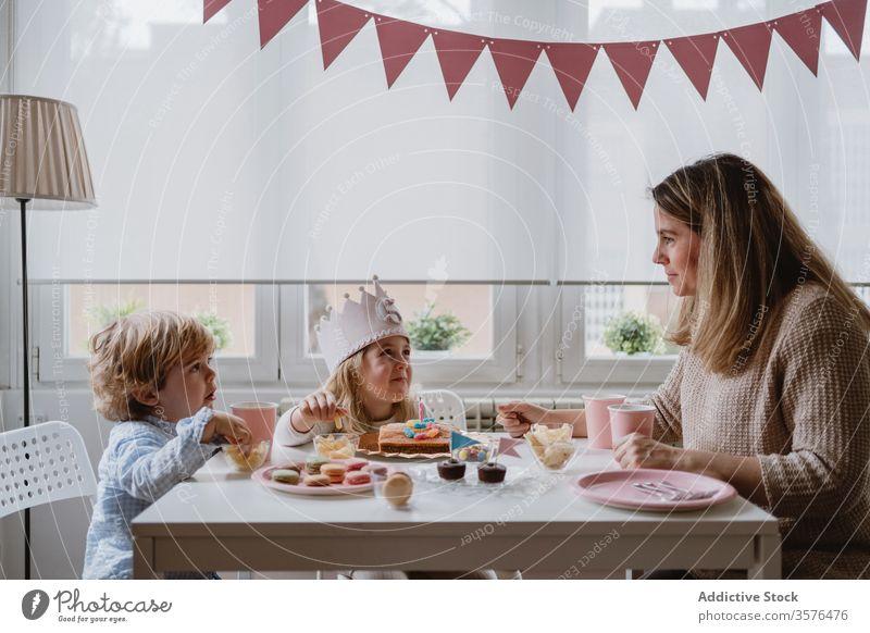 Positive Mutter spielt mit Kindern während einer Geburtstagsfeier zu Hause heimwärts Glück feiern Party Spaß Eltern Geschwisterkind Mädchen Junge Zusammensein