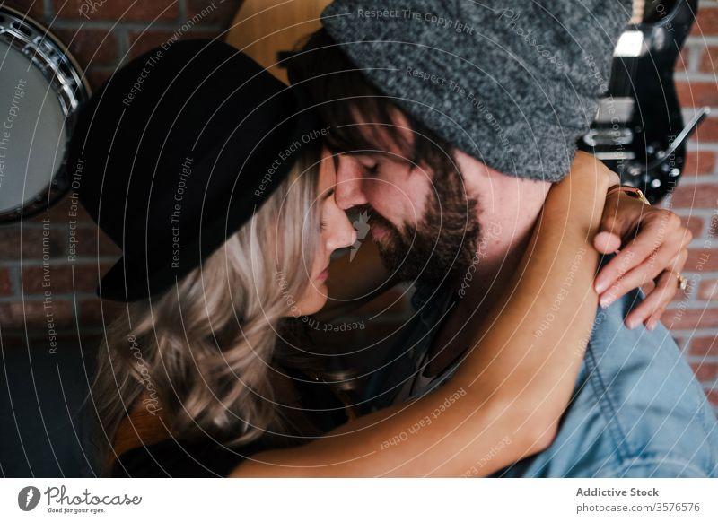 Paar umarmt sich auf dem Sofa in der Wohnung Umarmen Kuss Hipster Loft Partnerschaft Liebe Innenbereich Musiker Freund Zuneigung Zusammensein Augen geschlossen