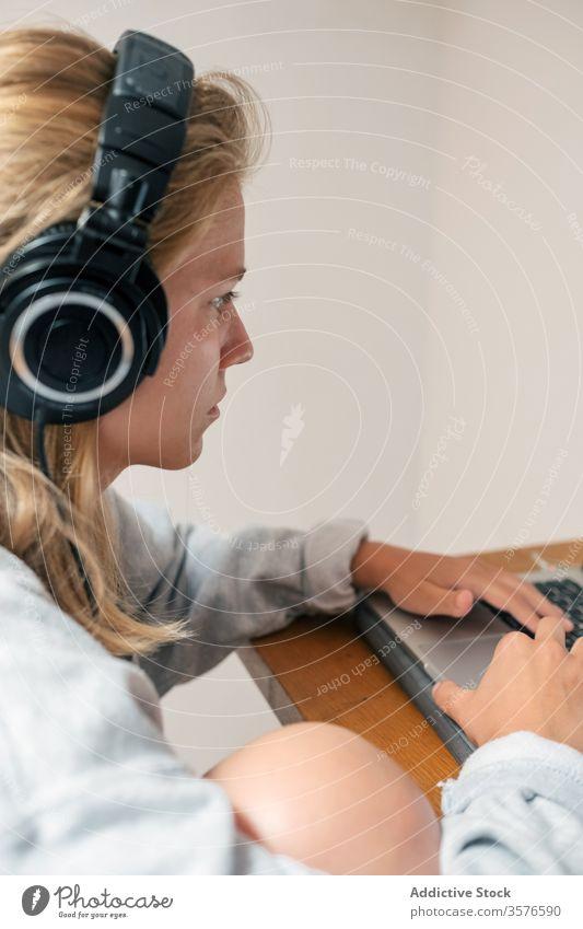 Junge Frau mit Kopfhörern am Laptop benutzend heimwärts Spieler lässig jung Browsen zuhören Apparatur ernst Fokus Gerät spielen Computer Lifestyle Internet