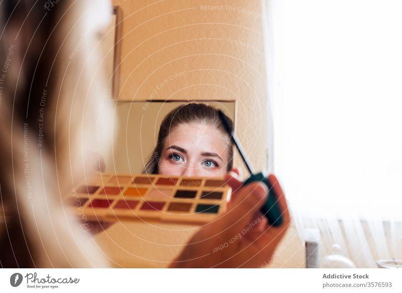 Junge Frau trägt Wimperntusche auf Make-up Kosmetik bewerben Schönheit Spiegel heimwärts dekorativ Palette Lidschatten lässig jung Pflege Routine Vorschein Auge