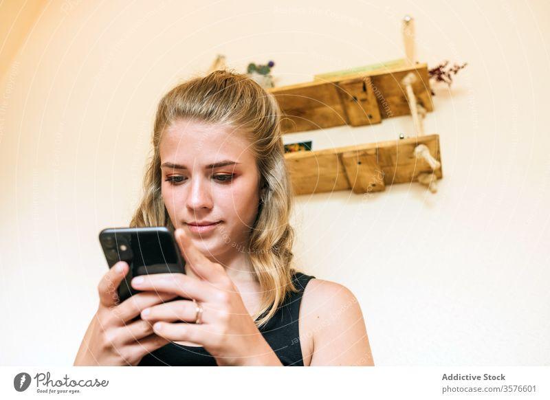 Junge Frau benutzt zu Hause ein Mobiltelefon Smartphone heimwärts benutzend jung lässig Telefon Browsen Nachricht positiv Apparatur Mobile Internet