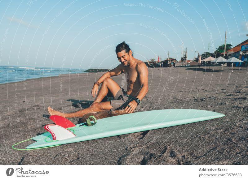 Männlicher Surfer mit Hund, der sich am Strand ausruht Mann ruhen Zusammensein Haustier Sand sitzen Freund Surfbrett Begleiter jung ohne Hemd männlich Sommer