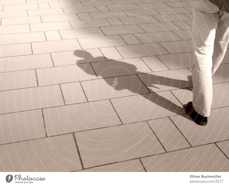 Schattenmann Mann Bürgersteig gehen Beine laufen Bodenbelag Pflastersteine