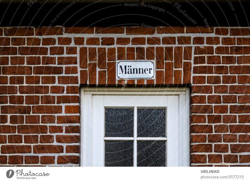 Text auf einem Emaileschild über einer Tür mit Sprossenfenster  trägt die Aufschrift Männer Backsteinwand Fassade Schriftzug Schriftzeichen Mauer Buchstaben