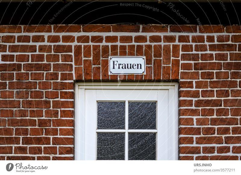 Frauen als Schriftzug auf einem Emaileschild über einer Glastür an einer Backsteinwand Tür Fenster Toilette Toilettenschild menschenleer Farbfoto alt Mauer