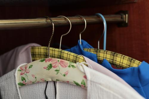 Blick in einen Kleiderschrank. Gemusterte Vintage Kleiderbügel und Frauenkleidung. Mode. bluse kleiderbügel geblümt kariert vintage nachhaltigkeit mode hängen