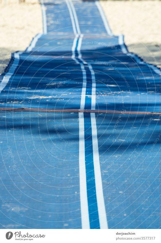 Ausgerollt. Langer blauer Läufer mit weißen Streifen, mit Falten, liegt am Srand zum Zugang zum Meer nur für Behinderte.. Teppich Läufer Bodenbelag