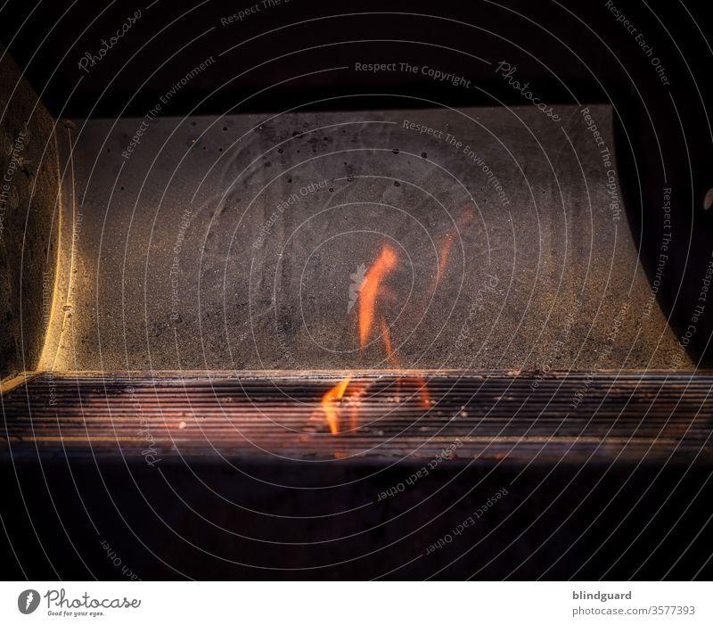 Eternal Flame. Flammen die über den Grillrost hinauszüngeln, während die Kohle im Grill angezündet wird und die Sonne harte Schlagschatten wirft Grillen lodern