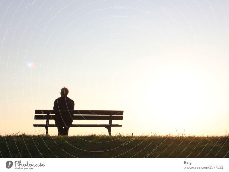 Silhouette eines Seniors, der in der Abendsonne auf einer Bank sitzt und in die Ferne schaut Mann sitzen Sonnenlicht Gegenlicht Gras männlich Licht Schatten