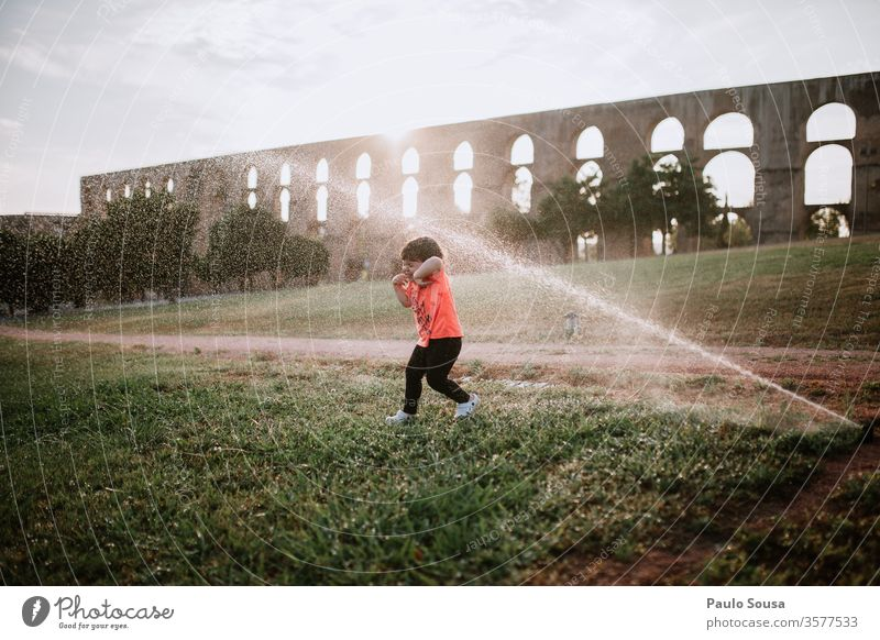 Mit Wassersprinklern spielende Kinder bestäuben Sommer Sommerurlaub Kinderspiel Kindheit Außenaufnahme Spielen Farbfoto Ferien & Urlaub & Reisen Freude