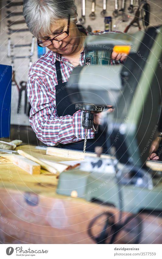 Ältere Frau in einer Tischlerei Senior Zimmerer Handwerkerin Werkstatt bohren arbeiten Holz reif Business Kaukasier heimwärts Schreinerei Ruhestand Arbeiter