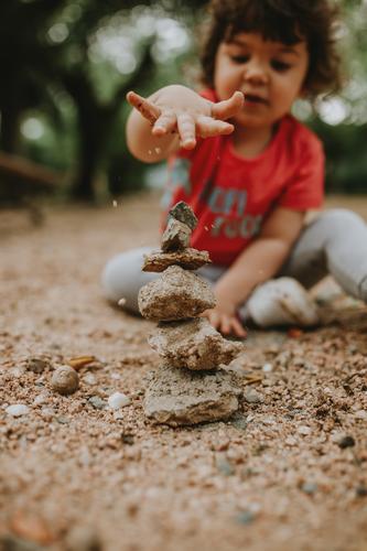Mit Sand spielendes Kind Steine Kinderspiel Kindheit Spielen im Freien Natur Ausgeglichenheit Gleichgewicht abgestimmt Farbfoto Außenaufnahme Freude