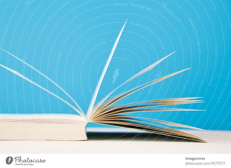 offenes Buch Nahaufnahme. Buch aufgeschlagen auf blauem Hintergrund. Lesen, Bildung, Literatur, Lernen und Schulanfang Konzept. Archiv zurück in die Schule