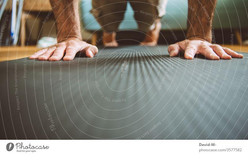 Fitnessübungen - Liegestütze zu Hause Mann liegestütze sportmatte Hände Kraft Krafttraining Ausdauer diszipliniert ehrgeizig motiviert Vorsätze abnehmen