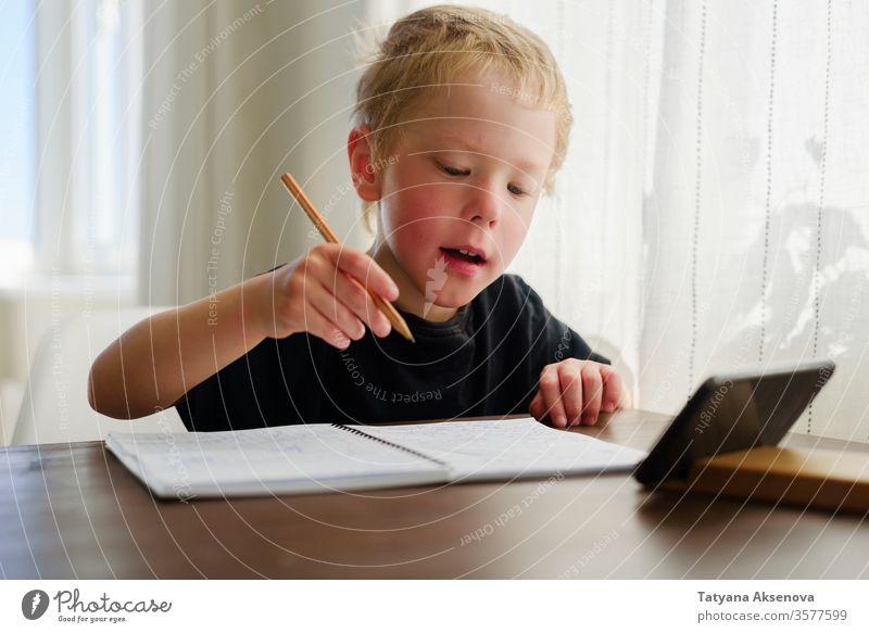 Kleiner Junge lernt zu Hause. Webinar per Handy anschauen, schreiben Bildung Homeschooling Kind online Lernen E-Learning heimwärts Entfernung Begeisterung