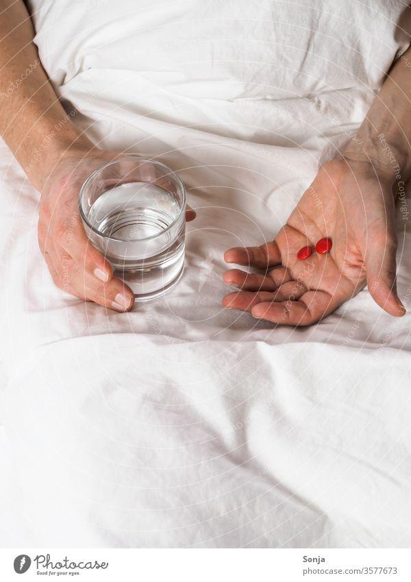 Mann hält ein Glas Wasser und Tabletten in der Hand im Bett krankheit trinkglas Coronavirus zu Hause bleiben Quarantäne covid-19 Prävention Infektion Virus