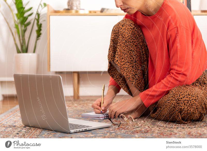 Junge Frau sitzt auf dem Teppich und arbeitet bei sich zu Hause. Sitzen arbeiten studierend heimwärts Innenbereich schön Porträt Raum Blick Erwachsener Internet