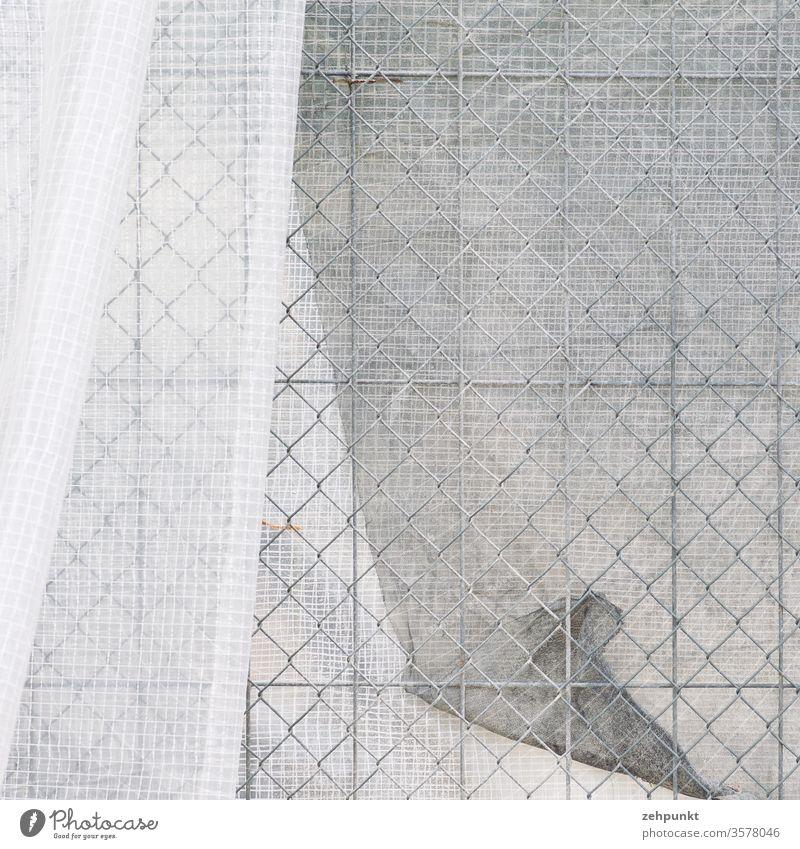 Grau in Grau: Eine weisse Sichtschutzmatte wirft Falten an einem Gitterbauzaun Bauzaun Muster Rautenmuster grau Folie Faltenwurf weiß Strukturen & Formen