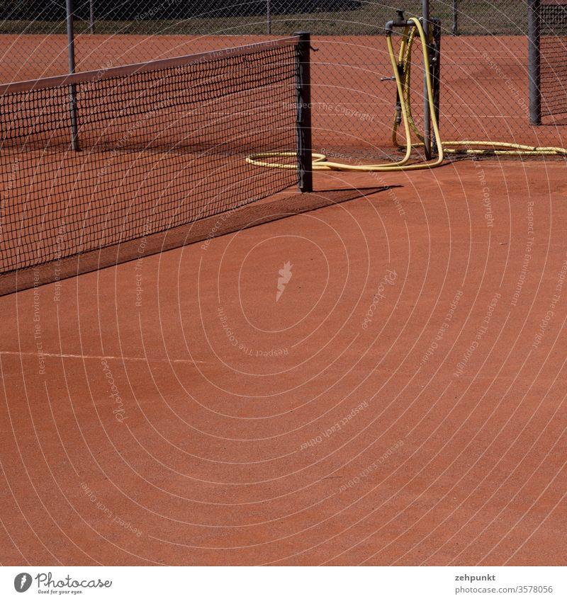 Ausschnitt von einem Tennisplatz mit Teilen des Netzen, rotem Sand, gelbem Wasserschlauch, schmaler Schattenwurf des Netzes schwarz Leerraum Menschenleer Sport