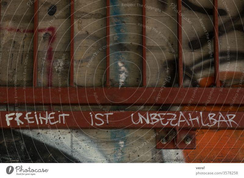 Schrift: Freiheit ist... Farbfoto Menschenleer Außenaufnahme Textfreiraum unten authentisch Zentralperspektive Tag Straße Kleinstadt Symbole & Metaphern