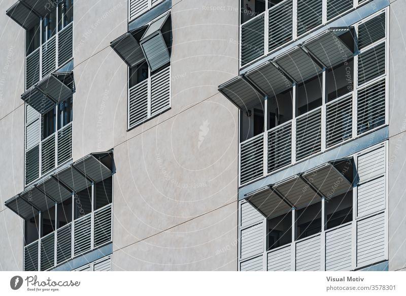Metallische Klappläden an der Fassade eines modernen Wohngebäudes Gebäude Fenster metallisch Fensterladen Außenseite Falten gefaltet sonnig tagsüber urban
