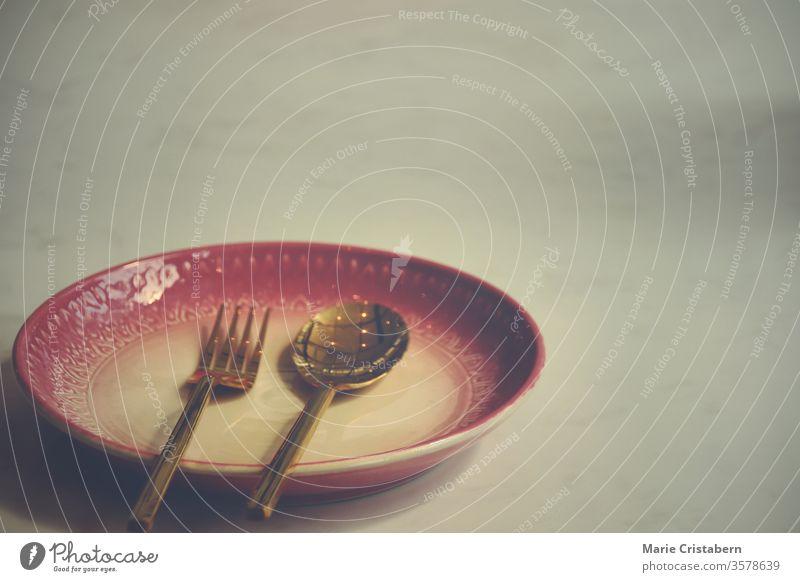 Ein leerer Teller in einem geschlossenen Restaurant zeigt die Einsamkeit, Wirtschaftskrise und Depression, die durch soziale Distanzierung, Abschottung und Selbstisolation aufgrund der Covid-19-Pandemie hervorgerufen werden.