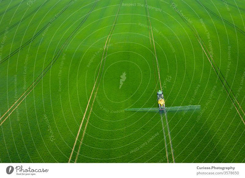 Grüne Felder. Luftaufnahme des Traktors, der die Chemikalien auf der großen grünen Wiese versprüht. Landwirtschaftlicher Frühlingshintergrund. Bereiche oben