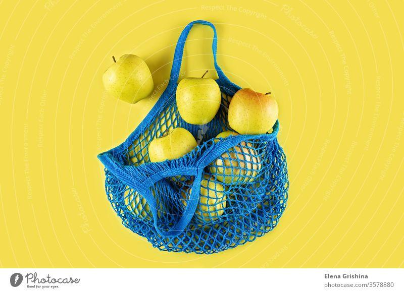 Reife Äpfel in einer blauen Schnurtüte auf gelbem Grund. keine Verschwendung Öko-Tasche Netzbeutel Apfel Baumwolle Einkaufsnetz Ökologie Konzept ökologisch