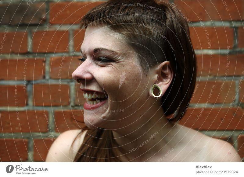 Portrait einer lachenden, jungen Frau vor einer Backsteinwand Spaß frei wild Freude heiter zuversichtlich Vertrauen Textfreiraum rechts Coolness