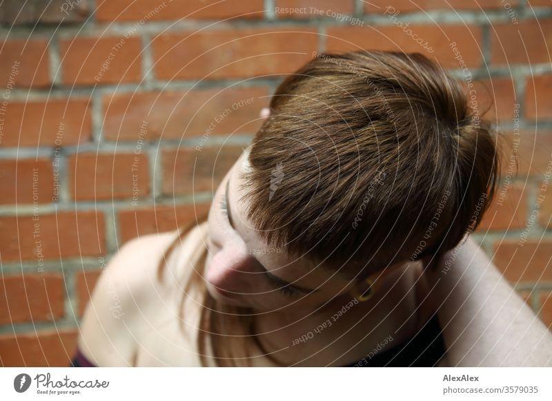 Portrait einer jungen Frau vor einer Backsteinwand frei wild heiter zuversichtlich Vertrauen Textfreiraum rechts Coolness Textfreiraum links Porträt