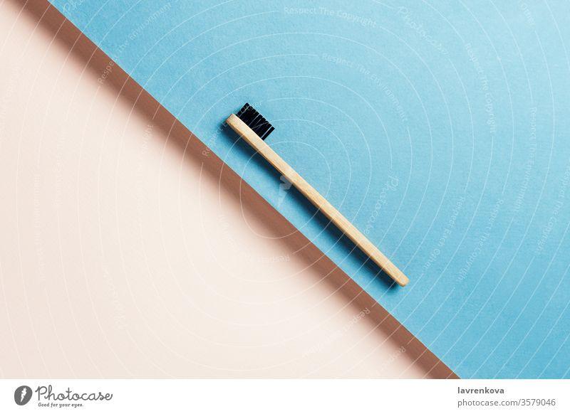Umweltfreundliche, nachhaltige Zahnbürste aus Bambuskohle auf blauem und pfirsichfarbenem Hintergrund, selektiver Fokus minimalistisch flache Verlegung Bad