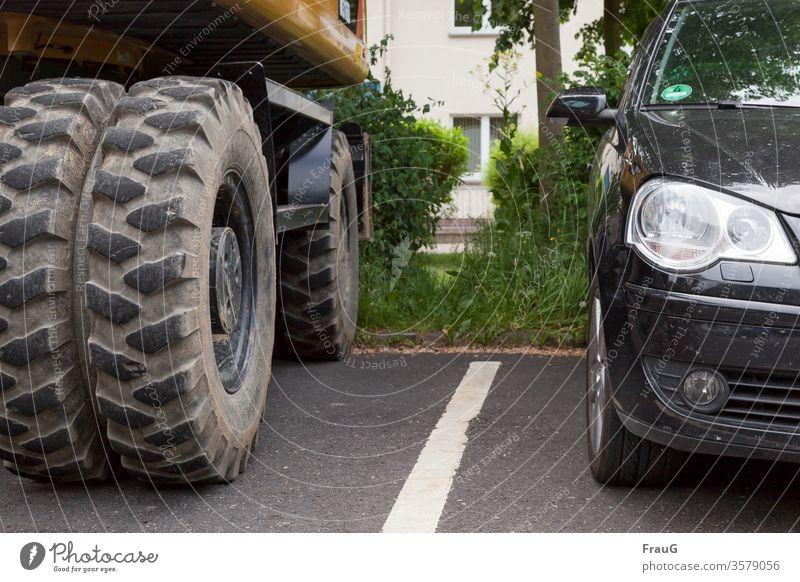 Zwischenräume  große und kleine Reifen PKW Baufahrzeug Bagger Reifenprofil Fahrzeuge groß und klein Straße Markierungslinie geparkt Spiegelung halb Zwischenraum